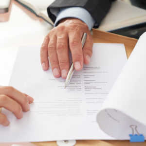 Close-up of business people examining business resume at the table during a job interview